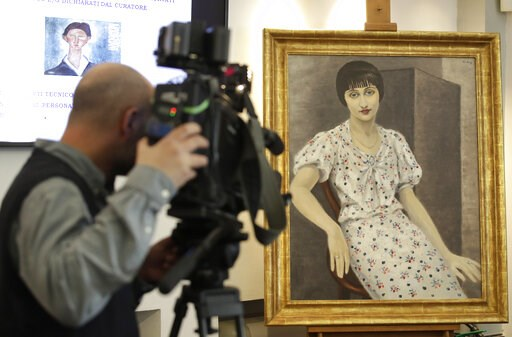 """(AP Photo/Alessandra Tarantino). A cameraman films a painting, """"Portrait of Kiki"""", falsely attributed to 20th century painter Moise Kisling, during a press conference announcing the conclusion of the preliminary phase of an investigation of 21 painting..."""