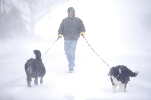 (Jacob Byk/The Wyoming Tribune Eagle via AP). Tom Skaar of Cheyenne laughs while walking his dogs on House Avenue during a blizzard on Wednesday, March 13, 2019, in Cheyenne, Wyo. White-out conditions closed I-80, I-25, and U.S. 85, effectively closing...