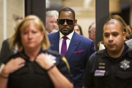 (Ashlee Rezin/Chicago Sun-Times via AP). R. Kelly walks out of The Daley Center after an appearance in court for his child support case, Wednesday, March 13, 2019, in Chicago.
