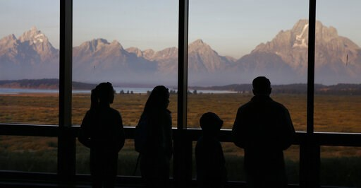 (AP Photo/Brennan Linsley,File). FILE - In this Aug. 28, 2016 file photo visitors watch the morning sun illuminate the Grand Tetons from within the Great Room at the Jackson Lake Lodge, in Grand Teton National Park, north of Jackson Hole, Wyo. Grand Te...