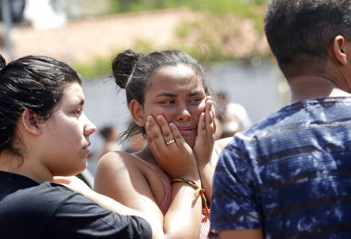 (AP Photo/Andre Penner). A student cries outside the Raul Brasil State School in Suzano, the greater Sao Paulo area, Brazil, Wednesday, March 13, 2019. The state government of Sao Paulo said two teenagers, armed with guns and wearing hoods, entered the...