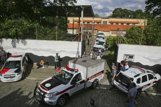 (AP Photo/Andre Penner). Forensic vehicles transport the bodies of the people who were killed in a school shooting at the Raul Brasil State School in Suzano, in the greater Sao Paulo area, Brazil, Wednesday, March 13, 2019. Two masked former students a...