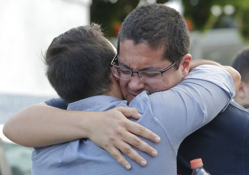 (AP Photo/Andre Penner). Vinicius Umezo, right, son of Marilena Umezo, an employee of the Raul Brasil State School, who was killed during the shooting, is comforted by a relative, in Suzano on the greater Sao Paulo area, Brazil, Wednesday, March 13, 20...