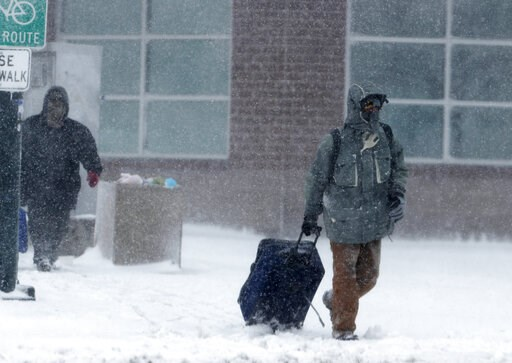 (AP Photo/David Zalubowski). A traveller drags a suitcase as a late winter storm packing hurricane-force winds and snow sweeps over the intermountain West Wednesday, March 13, 2019, in Denver.