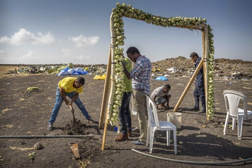 (AP Photo/Mulugeta Ayene). Workers erect floral installations at the scene where the Ethiopian Airlines Boeing 737 Max 8 crashed shortly after takeoff on Sunday killing all 157 on board, near Bishoftu, or Debre Zeit, south of Addis Ababa, in Ethiopia W...