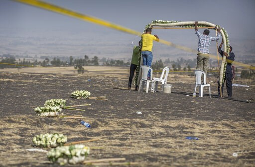 (AP Photo/Mulugeta Ayene). Wreaths and floral installations are placed near wreckage at the scene where the Ethiopian Airlines Boeing 737 Max 8 plane crashed shortly after takeoff on Sunday killing all 157 on board, near Bishoftu, or Debre Zeit, south ...