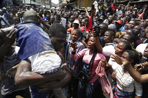 (AP Photo/Sunday Alamba). A child is rescued from the rubble of a collapsed building in Lagos, Nigeria, Wednesday, March 13, 2019. Rescue efforts are underway in Nigeria after a three-story school building collapsed while classes were in session, with ...