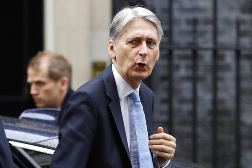 (AP Photo/Kirsty Wigglesworth). Britain's Chancellor Philip Hammond arrives at Downing Street in London, Thursday, March 14, 2019. In a tentative first step toward ending months of political deadlock, British lawmakers voted Wednesday to block the coun...