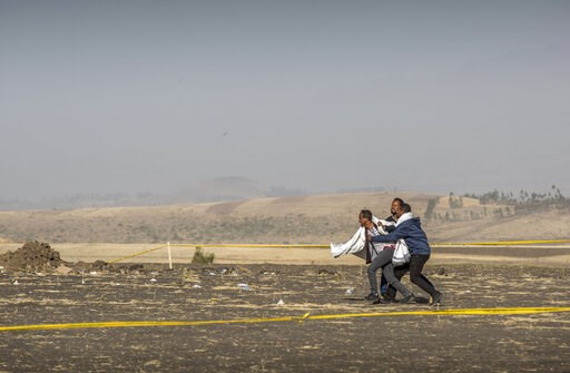 (AP Photo/Mulugeta Ayene). A grieving relative is held back by others at the scene where the Ethiopian Airlines Boeing 737 Max 8 crashed shortly after takeoff on Sunday killing all 157 on board, near Bishoftu, or Debre Zeit, south of Addis Ababa, in Et...