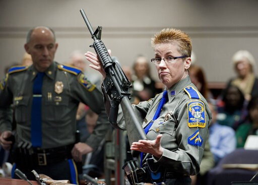 (AP Photo/Jessica Hill, File). FILE - In this Jan. 28, 2013, file photo, firearms training unit Detective Barbara J. Mattson, of the Connecticut State Police, holds a Bushmaster AR-15 rifle, the same make and model used by Adam Lanza in the 2012 Sandy ...