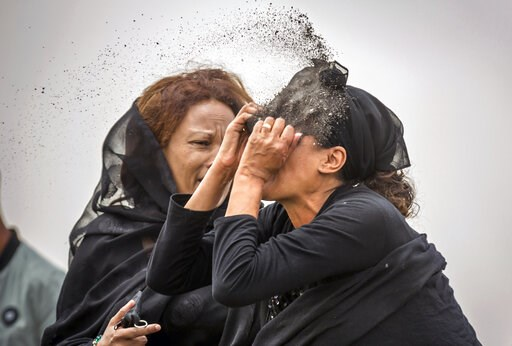 (AP Photo/Mulugeta Ayene). An Ethiopian relative of a crash victim throws dirt in her own face after realising that there is nothing physical left of her loved one, as she mourns at the scene where the Ethiopian Airlines Boeing 737 Max 8 crashed shortl...