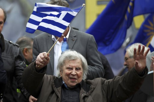 """(AP Photo/Petros Giannakouris, File). FILE - In this Sunday, Feb. 4, 2018 file photo, famous Greek composer Mikis Theodorakis holds a Greek flag waves after his speech at a rally in Athens. """"Zorba the Greek"""" composer Mikis Theodorakis has undergone sur..."""