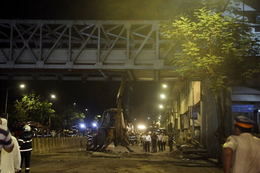(AP Photo/Rajanish Kakade). A crane works to remove a pedestrian bridge after a part of it collapsed in Mumbai, India, Thursday, March 14, 2019. A pedestrian bridge connecting a train station with a road collapsed in Mumbai on Thursday, killing at leas...
