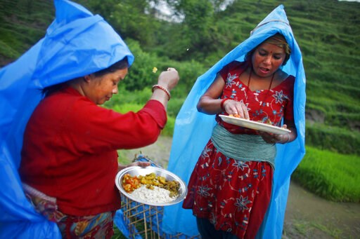 (AP Photo/Niranjan Shrestha). FILE - In this June 30, 2014 file photo, a farmer, left, ritualistically offers a small portion of food to god before eating her lunch while working at a rice field in Chunnikhel, Katmandu, Nepal. Languages evolve as socie...