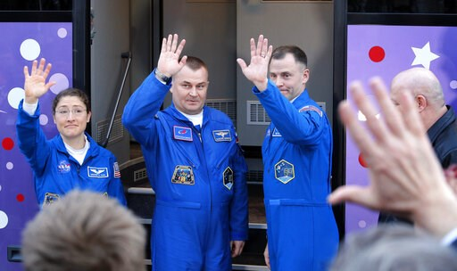 (AP Photo/Dmitri Lovetsky). U.S. astronauts Christina Hammock Koch, left, Nick Hague, right, and Russian cosmonaut Alexey Ovchinin, members of the main crew to the International Space Station (ISS), pose near a bus prior to the launch of the Soyuz FG r...