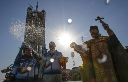 (AP Photo/Dmitri Lovetsky). An Orthodox priest conducts a blessing service in front of the Soyuz FG rocket at the Russian leased Baikonur cosmodrome, Kazakhstan, Thursday, March 14, 2019. The new Soyuz mission to the International Space Station (ISS) i...