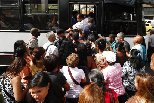 (AP Photo/Eduardo Verdugo). Passengers scramble to board a bus in Caracas, Venezuela, Thursday, March 14, 2019. With long lines at the stops of public transport and crowds of people at the entrance of some banking agencies, Venezuelans returned to acti...