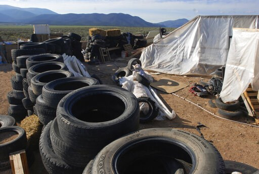 (AP Photo/Morgan Lee, File). FILE - In this Aug. 10, 2018, file photo, is a makeshift living compound in Amalia, N.M. The five men and women found living in a ramshackle compound in northern New Mexico where a boy was found dead last year have been ind...