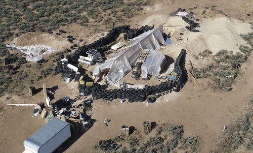 (AP Photo/Brian Skoloff, File). FILE - This Aug. 10, 2018, file photo shows a ramshackle compound in the desert area of Amalia, N.M. The five men and women found living in a ramshackle compound in northern New Mexico where a boy was found dead last yea...