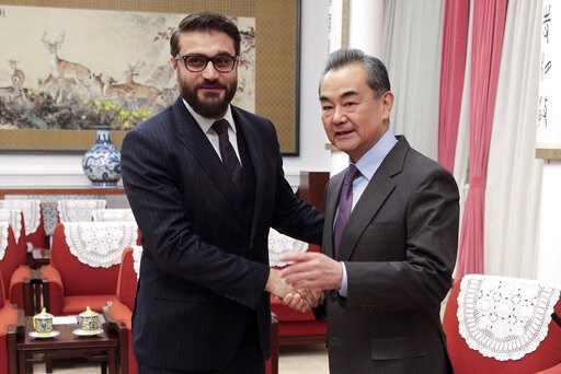 (AP Photo/Andy Wong, Pool). FILE - In this Jan. 10, 2019, file photo, Afghanistan national security adviser Hamdullah Mohib, left, shakes hands with Chinese Foreign Minister Wang Yi before proceeding to their meeting at the Zhongnanhai Leadership Compo...