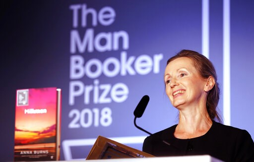 "(AP Photo/Frank Augstein, File). FILE - In this Oct. 16, 2018 file photo, author Anna Burns smiles after being presented with the Man Booker Prize for Fiction 2018 for ""Milkman,"" during the prize's 50th year at the Guildhall in London. Burns' ""Milkman""..."