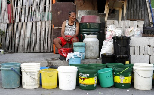 (AP Photo/Aaron Favila). A man sits beside rows of pails as he waits for water trucks return to their area after several days without water in Mandaluyong, metropolitan Manila, Philippines on Thursday, March 14, 2019. Aside from the daily line of resid...