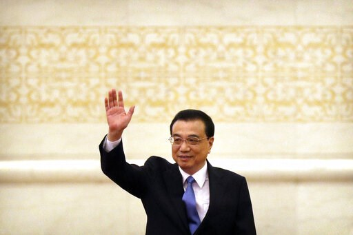 (AP Photo/Mark Schiefelbein). Chinese Premier Li Keqiang waves as he arrives for a press conference held after the closing session of China's National People's Congress (NPC) at the Great Hall of the People in Beijing, Friday, March 15, 2019.