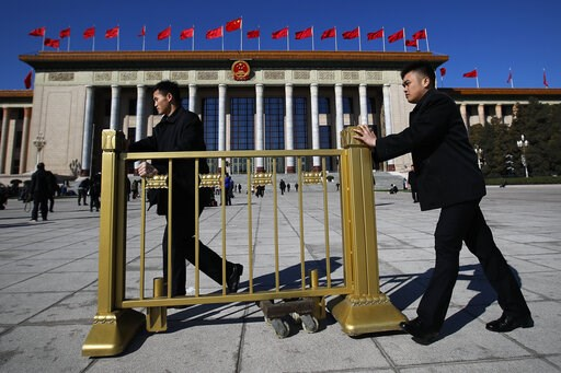 (AP Photo/Andy Wong). Soldiers in usher uniforms push a barricade as they prepare to close off the Great Hall of the People after the closing session of China's National People's Congress (NPC) in Beijing, Friday, March 15, 2019.