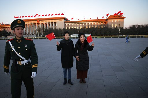(AP Photo/Andy Wong). Chinese women pose with national flags in front of the Great Hall of the People as paramilitary policemen try to clear Tiananmen Square after the daily flag raising ceremony before the closing session of China's National People's ...