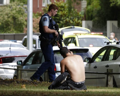 (AP Photo/Mark Baker). A man rests on the ground as he speaks on his mobile phone across the road from mosque in central Christchurch, New Zealand, Friday, March 15, 2019. A witness says a number of people have been killed in a mass shooting at a mosqu...