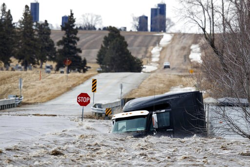 (Ryan Soderlin/Omaha World-Herald via AP). A semi truck and trailer are swept off the road by floodwaters Thursday, March 13, 2019, in Arlington, Neb. Evacuations forced by flooding have occurred in several eastern Nebraska communities, as western Nebr...