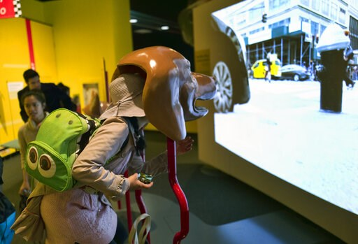 (AP Photo/Richard Vogel). In this Tuesday, March 12, 2019 photo, a visitor takes part in an immersive experience showing visitors how dogs see from inside the head of a dog at the California Science Center in Los Angeles. A new exhibit at a Los Angeles...