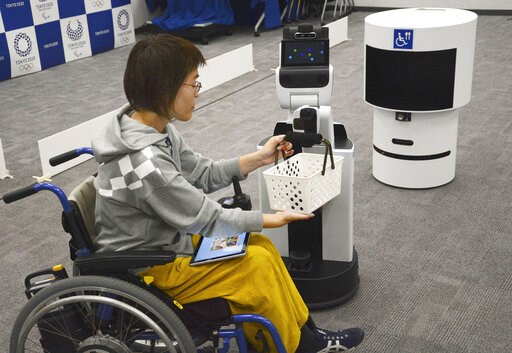 (Kyodo News via AP). A robot passes a basket containing drinks to a woman in wheelchair during an unveiling event in Tokyo Friday, March 15, 2019. Organizers on Friday showed off robots that will be used at the new National Stadium to provide assistanc...