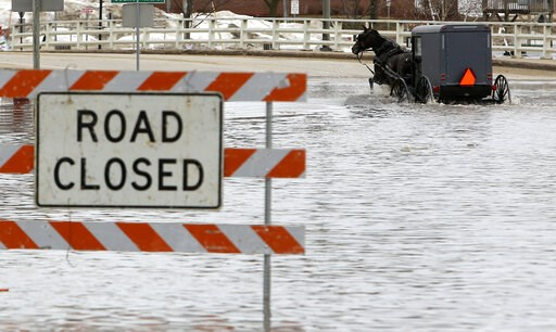 (Dave Kettering/Telegraph Herald via AP). A man works his way through a flooded Galena Street as the Pecatonica River continues to rise in Darlington, Wis., Thursday, March 14, 2019.  The National Weather Service has issued a flood warning or flood wat...