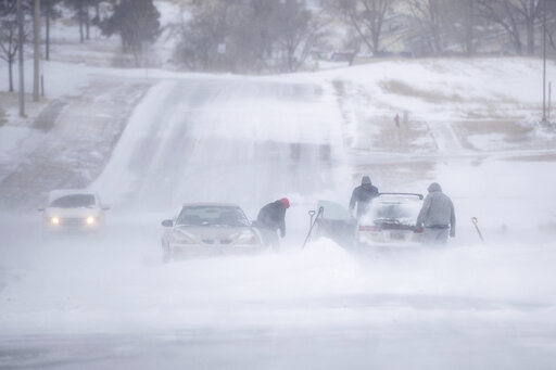 (Ryan Hermens/Rapid City Journal via AP). People work to free a vehicle from a snow drift in north Rapid City, S.D., Thursday, March 14, 2019. All state offices are now closed in South Dakota as blizzard conditions barrel into the Midwest.