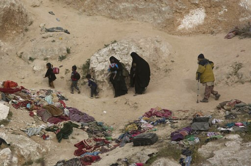 (AP Photo/Maya Alleruzzo). Women, children, and an injured man who left the besieged Islamic State-held village of Baghouz, Syria, scramble over a rocky hillside to be checked by U.S-backed Syrian Democratic Forces, Thursday, March 14, 2019.