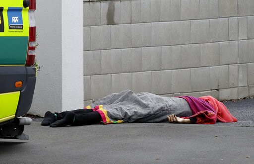 (AP Photo/Mark Baker). A body lies on the footpath outside a mosque in central Christchurch, New Zealand, Friday, March 15, 2019, following a mass shooting.