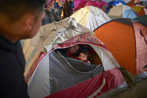 (AP Photo/Gregory Bull). In this March 5, 2019, image, Ruth Aracely Monroy, center, looks out of the family's tent alongside her 10-month-old son, Joshua, as her husband, Juan Carlos Perla, left, passes inside a shelter for migrants in Tijuana, Mexico....
