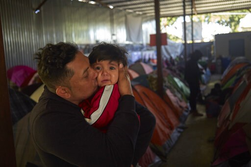 (AP Photo/Gregory Bull). In this March 5, 2019, image, Juan Carlos Perla kisses his 10-month-old son, Joshua, inside a shelter for migrants in Tijuana, Mexico. After fleeing violence in El Salvador and requesting asylum in the United States, the family...