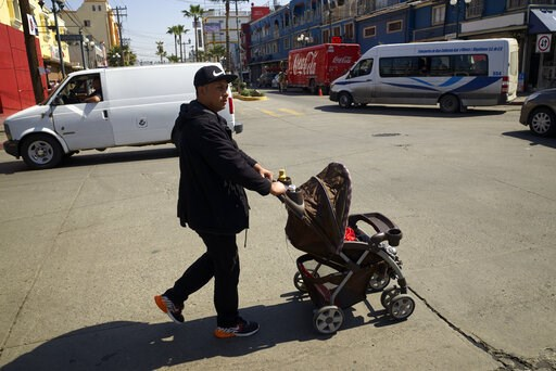 (AP Photo/Gregory Bull). In this March 5, 2019, image, Juan Carlos Perla pushes his youngest son, Joshua, in a stroller along a street in Tijuana, Mexico. Perla's experience suggests that a new policy forcing asylum seekers to wait in Mexico may be hav...