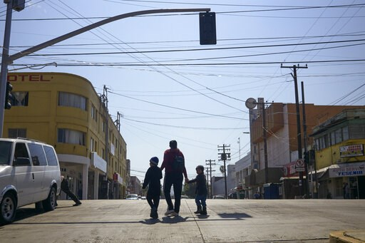 (AP Photo/Gregory Bull). In this March 5, 2019, image, Ruth Aracely Monroy walks with her sons in Tijuana, Mexico. After requesting asylum in the United States, the family was returned to Tijuana to wait for their hearing in San Diego. They were one of...