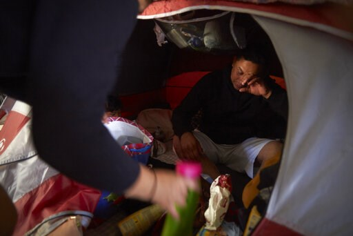 (AP Photo/Gregory Bull). In this March 5, 2019, image, Juan Carlos Perla reacts as he and his wife, Ruth Aracely Monroy, left, searches for medicine in their tent for their 10-month-old son with a cold inside a shelter for migrants in Tijuana, Mexico. ...