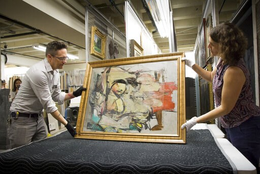 "(Robert Demers/University of Arizona Communications via AP). This August 2017 photo shows ""Woman-Ochre,"" a painting by Willem de Kooning, being readied for examination by University of Arizona Museum of Art staff Nathan Saxton, left, and Kristen Schmid..."