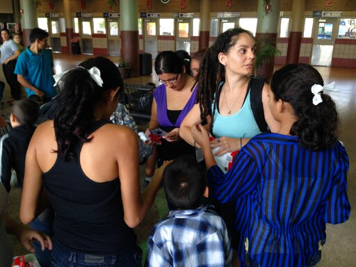 (AP Photo/Valeria Fernández, File). File - In this May 29, 2014 file photo, volunteer Layal Rabat from the Phoenix Restoration Project brings water, food and diapers to Central-American women and their children dropped off at the Greyhound bus station ...