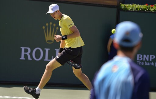 (AP Photo/Mark J. Terrill). Hubert Hurkacz, of Poland, hits a shot between his legs to Roger Federer, of Switzerland, at the BNP Paribas Open tennis tournament Friday, March 15, 2019, in Indian Wells, Calif.