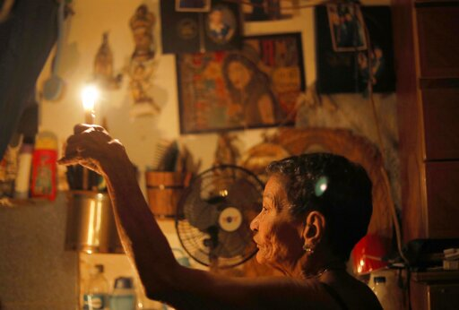 "(AP Photo/Ariana Cubillos). 72-year-old Elizabeth Guzman Espitia holds a candle in herwindowless room she calls her ""little cave"" during a blackout in the Santa Cruz of the East neighborhood, in Caracas, Venezuela, Thursday, March 14, 2019. I've never ..."