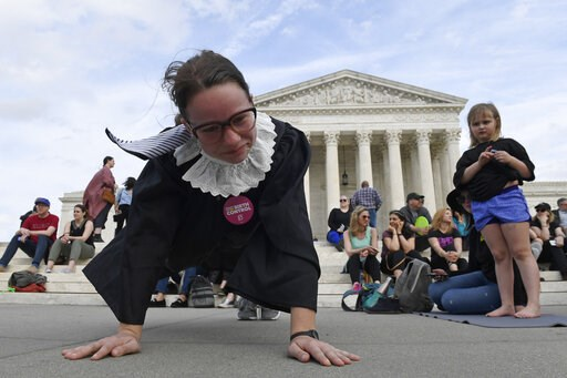 (AP Photo/Susan Walsh). Alice Wisbiski, dressed as Supreme Court Associate Justice Ruth Bader Ginsburg, is joined by others as a group do exercises on the steps of the Supreme Court in Washington, Friday, March 15, 2019, to celebrate Ginsburg's upcomin...