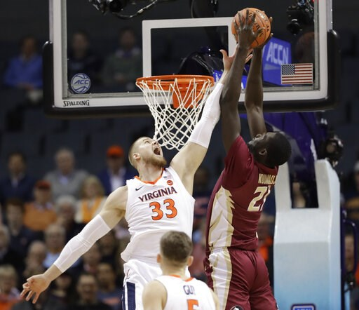 (AP Photo/Chuck Burton). Florida State's Christ Koumadje (21) tries to dunk against Virginia's Jack Salt (33) during the first half of an NCAA college basketball game in the Atlantic Coast Conference tournament in Charlotte, N.C., Friday, March 15, 2019.
