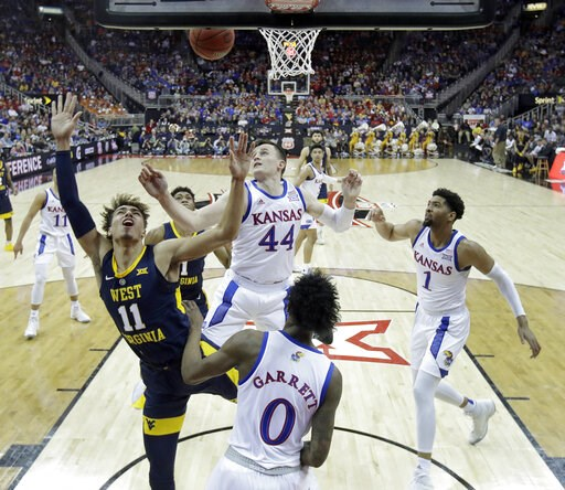 (AP Photo/Charlie Riedel). West Virginia's Emmitt Matthews Jr. (11) gets past Kansas' Mitch Lightfoot (44) to put up a shot during the first half of an NCAA college basketball game in the Big 12 men's tournament Friday, March 15, 2019, in Kansas City, ...