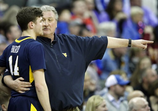 (AP Photo/Orlin Wagner). West Virginia head coach Bob Huggins talks with guard Chase Harler (14) during the first half of an NCAA college basketball game in the semifinals of the Big 12 conference tournament in Kansas City, Mo., Friday, March 15, 2019.